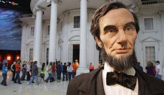 """In this Feb. 10, 2012 file photo, school students enter the """"White House"""" as a life-size Abraham Lincoln replica stands outside, while touring the Abraham Lincoln Presidential Library and Museum in Springfield, Ill. The chairman of the foundation behind the Library and Museum says fundraising is drying up because of tensions between library directors and the state agency that oversees it. (AP Photo/Seth Perlman, File)FILE -"""