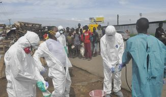 Onlookers watch as health workers in protective gear sprayed each other with disinfectant after they removed the body of a woman suspected of dying from Ebola virus, near the area of Freeport in Monrovia, Liberia, Wednesday, Oct. 1, 2014. The first case of Ebola diagnosed in the U.S. has been confirmed in a man who recently traveled from Liberia to Dallas. (AP Photo/Abbas Dulleh)