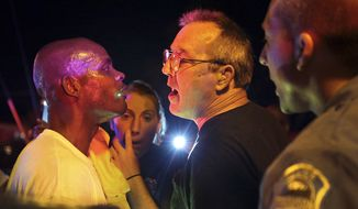 Larry Claffy, right, of Overland and a patron of Faraci Pizza in Ferguson, Mo., has words with a protester as police move in to break up the confrontation on Tuesday, Sept. 30, 2014. There has been unrest in the St. Louis suburb since the Aug. 9 shooting of Michael Brown, an unarmed, black 18-year-old, by a white police officer. (AP Photo/St. Louis Post-Dispatch, Robert Cohen)