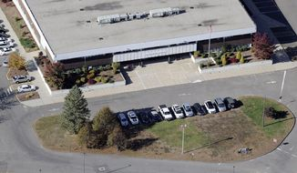 This Oct. 28, 2013, aerial photo shows the Sandy Hook Elementary School, relocated to the former Chaulk Hill School building in Monroe, Conn., after the original building in neighboring Newtown was razed following a Dec. 14, 2012, shooting rampage where 26 people were killed. A threat Wednesday, Oct. 1, 2014, led to the evacuation of the new Sandy Hook Elementary School in Monroe. The superintendent's office said the students were being moved to a nearby school where they could be picked up by their parents. (AP Photo/Jessica Hill)