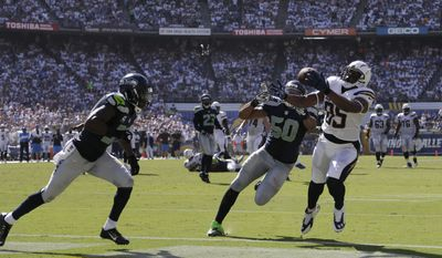 San Diego Chargers tight end Antonio Gates hauls in a touchdown catch as Seattle Seahawks outside linebacker K.J. Wright (50) and strong safety Kam Chancellor (31) defend during the second half of an NFL football game on Sunday, Sept. 14, 2014, in San Diego. (AP Photo/Gregory Bull)