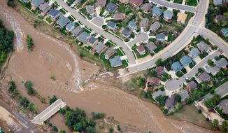 Floodwaters cut a residential neighborhood in two last year in Lyons, Colorado. Thousands of people living along Front Range were forced to evacuate. The freak storm, however, was not a result of man-made climate change, a scientific study shows. (Associated Press)