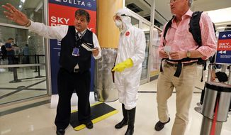 Two days after a man in Texas was diagnosed with Ebola, Dr. Gil Mobley, a Missouri doctor, checks in to board a plane dressed in full protection gear Thursday morning, Oct. 2, 2014, at Hartsfield-Jackson Atlanta International Airport. He was protesting what he called mismanagement of the crisis by the federal Centers for Disease Control and Prevention. (AP Photo/Atlanta Journal-Constitution, John Spink)