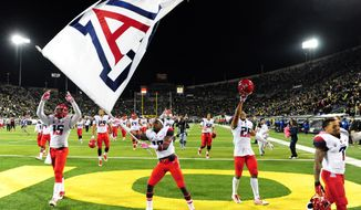 Arizona players celebrate after beating Oregon in the NCAA college football game at Autzen Stadium on Thursday, Oct. 2, 2014, in Eugene, Ore. Arizona won the game 31-24.(AP Photo/Steve Dykes)