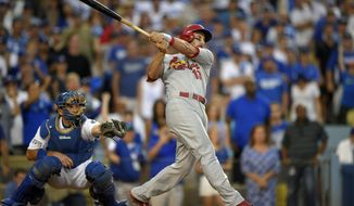 St. Louis Cardinals' Matt Carpenter, right, hits a three-RBI double as Los Angeles Dodgers catcher A.J. Ellis looks on in the seventh inning of Game 1 of baseball's NL Division Series in Los Angeles, Friday, Oct. 3, 2014. (AP Photo/Mark J. Terrill)