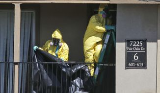 Hazardous material cleaners prepare to hang black plastic outside the apartment in Dallas, Friday, Oct. 3, 2014, where Thomas Eric Duncan, the Ebola patient who traveled from Liberia to Dallas stayed last week. The crew is expected to remove items including towels and bed sheets used by Duncan, who is being treated at an isolation unit at a Dallas hospital. The family living there has been confined under armed guard while being monitored by health officials. (AP Photo/LM Otero)