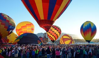 A balloon lifts off  over the crowd in the early morning during the annual Albuquerque International Balloon Fiesta in Albuquerque, N.M. Saturday, Oct.  4, 2014.  Organizers have equipped all 550 pilots with tablet computers capable of running a mapping application that will enable them to steer clear of the many restricted areas or prohibited zones like airport flight paths, the zoo and other locations. (AP Photo/The Albuquerque Journal, Jim Thompson)
