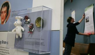 """In this photo taken on Thursday, Oct. 2, 2014, Tamara Martz, exhibit and graphic designer at the University of Alaska Museum of the North, hangs wall boards in the background as a case including the Pillsbury Doughboy doll, California Raisins figurines and Mr. Peanut nut bowl is on display as the """"Key Ingredients: America By Food"""" Smithsonian Institution traveling exhibit is installed at the UAF Community and Technical College on Barnette Street in Fairbanks, Alaska. (AP Photo/Fairbanks Daily News-Miner, Eric Engman)"""