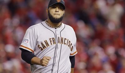 San Francisco Giants relief pitcher Yusmeiro Petit (52) pumps his fist as he walks off the field at the end of the 15th inning in Game 2 of baseball's NL Division Series against the Washington Nationals in Nationals Park, Saturday, Oct. 4, 2014, in Washington. (AP Photo/Patrick Semansky)