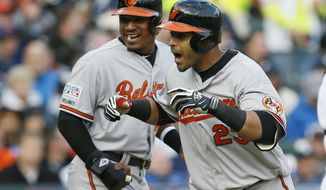 Baltimore Orioles' Nelson Cruz (23) celebrates with Adam Jones after Cruz hit a two-run home run during the sixth inning in Game 3 of baseball's AL Division Series against the Detroit Tigers, Sunday, Oct. 5, 2014, in Detroit. (AP Photo/Paul Sancya)