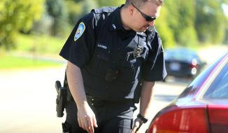 In this Sept. 22, 2014 file photo, detective Gordy Lauren, of the the Lowell police department, in Kent County, Mich., makes a routine traffic stop. (AP Photo/Detroit Free Press, Jessica J. Trevino) ** FILE **