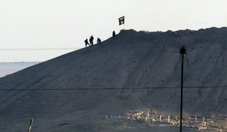 claim: Militants with the Islamic State plant a hilltop flag near the town of Kobani along the Syrian-Turkish border. (associated press)