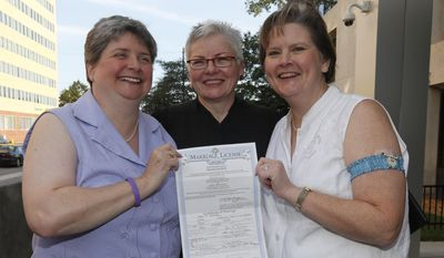 Sharon Baldwin, left, and Mary Bishop, right, pose for photos with their marriage certificate, and Oklahoma Court of Civil Appeals Judge Jane Wiseman, who officiated their wedding ceremony on the courthouse steps, in Tulsa, Okla., Monday, Oct. 6, 2014. Ms. Bishop and Ms. Baldwin were the lead plaintiffs who challenged Oklahoma's ban on same-sex marriage in 2004, shortly after 76 percent of Oklahoma voters approved the ban. The wedding came after the U.S. Supreme Court earlier Monday declined to take up the state's appeal in the case, and a federal appeals court lifted its stay. (AP Photo/Sue Ogrocki)