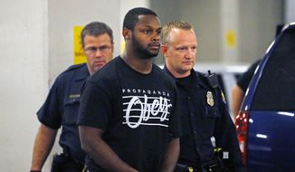 In this Sept. 17, 2014, file photo, Phoenix police officers escort Arizona Cardinals running back Jonathan Dwyer,  to the 4th Avenue Jail following his arrest in Phoenix. Dwyer is scheduled to be arraigned Monday, Oct. 6, 2014,  on charges that he assaulted his wife during two arguments in July at their Phoenix apartment.   (AP Photo/The Arizona Republic, David Kadlubowski, File)