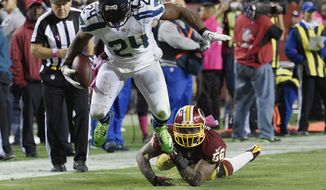 Seattle Seahawks running back Marshawn Lynch (24) breaks a tackle by Washington Redskins inside linebacker Perry Riley (56) on his way to a touchdown during the second half of an NFL football game in Landover, Md., Monday, Oct. 6, 2014. (AP Photo/Nick Wass)