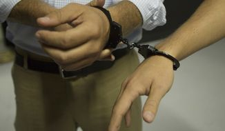 In this Sept. 22, 2014 photo, two people are handcuffed together as they start to play a game at Escape the Quest in Miami Beach, Fla. Escape the Quest offers two games; Apartment 101 and Prison Escape, where groups of two to four have an hour to solve a puzzle and win their freedom. (AP Photo/J Pat Carter)