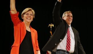 Massachusetts Sen. Elizabeth Warren, left, arrives with Oregon Sen. Jeff Merkley at a Merkley campaign rally, Monday, Oct. 6, 2014 on the University of Oregon campus in Eugene, Ore. It was Warren's second visit to Oregon in support of the incumbent Merkley who is running against Republican Dr. Monica Wehby. (AP Photo/The Register-Guard, Andy Nelson)