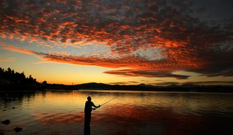 In this Friday, Oct. 3, 2014 photo, Delmar Parris, of Port Orchard, Wash., casts his fishing line off Bay Street in Port Orchard during a fall sunset. (AP Photo/Kitsap Sun, Larry Steagall)