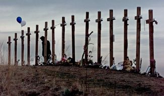 "FILE - This April 28, 1999 file photo shows a woman standing among 15 crosses posted on a hill above Columbine High School in Littleton, Colo., in remembrance of the 15 people who died during a school shooting on April 20. A play about the Columbine High School massacre written from the perspective of the two teen shooters will make its world premiere in New York next month, penned by a playwright who was 9 at the time of the killings and calls it ""a watershed moment."" (AP Photo/Eric Gay, file)"