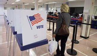 A woman walks past voting booths at the Cuyahoga County Board of Elections in Cleveland, Tuesday, Oct. 7, 2014. Early voting began in Ohio after the U.S. Supreme Court stepped into a dispute over the schedule, pushing the start date back a week in the swing state. (AP Photo/Mark Duncan) **FILE**