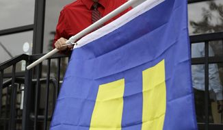 Logan Seven prepares to raise a an equality flag at the Chapelle de l'amore wedding chapel Tuesday, Oct. 7, 2014, in Las Vegas. The 9th U.S. Circuit Court of Appeals in San Francisco struck down the ban on same sex marriages in Nevada and Idaho on Tuesday. (AP Photo/John Locher)