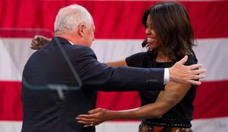 First lady Michelle Obama embraces Illinois Gov. Pat Quinn, left, before speaking at a political rally for Quinn on Tuesday, Oct. 7, 2014, at the UIC Pavilion in Chicago. Quinn faces opponent Republican gubernatorial candidate Bruce Rauner in the upcoming election. (AP Photo/Andrew A. Nelles)