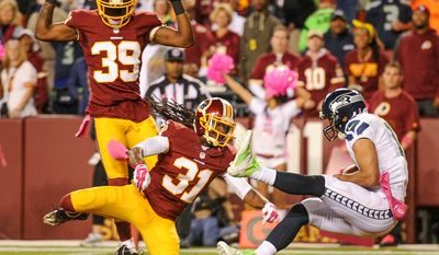 Seattle Seahawks wide receiver Jermaine Kearse (15) scores on a pass between Washington Redskins strong safety Brandon Meriweather (31) and Washington Redskins cornerback David Amerson (39) early in the first quarter as the Washington Redskins play the Seattle Seahawks in Monday Night Football at FedExField, Landover, Md., Monday, October 6, 2014. (Andrew Harnik/The Washington Times)