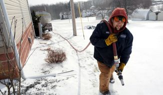 FILE - In this Jan. 7, 2014 file photo, Denver Walker, of Somerset Fuels, makes a heating oil delivery to a home in Jenner Crossroads, Pa. The Energy Department's annual prediction of winter heating costs released Tuesday, Oct. 7, 2014 says that Americans will pay less because they won't have to crank up the heat as much. (AP Photo/Tribune-Democrat, John Rucosky, File) MANDATORY CREDIT