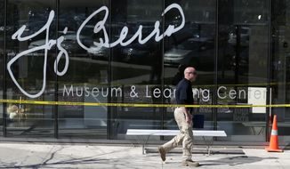 A Montclair State University police official walks by the Yogi Berra Museum while investigating a reported break-in, Wednesday, Oct. 8, 2014, in Montclair, N.J. (AP Photo/Julio Cortez)