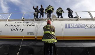 A Seattle firefighter climbs atop a training tank car to join others during a specialized training session on how to respond to incidents involving oil trains, Wednesday, Oct. 8, 2014, in Seattle. BNSF is training several dozen firefighters from Seattle and neighboring cities on how to use a new firefighting foam trailer that will be based in Seattle and on a variety of tank car valves and other equipment. (AP Photo/Elaine Thompson)