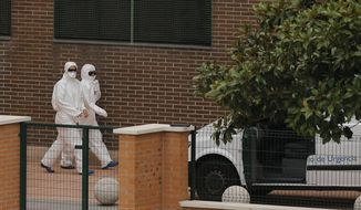 A vehicle of the veterinarian emergency service is parked outside of the apartment of the Spanish nurse infected with Ebola and where is believed  her dog remains as worker wearing protective suits and  gloves walk by in Madrid, Spain, Wednesday, Oct. 8, 2014. Three more people were placed under quarantine for Ebola at a Madrid hospital where a Spanish nurse became infected, authorities said . More than 50 other possible contacts were being monitored. The nurse, who had cared for a Spanish priest who died of Ebola, was the first case of Ebola being transmitted outside of West Africa, where a months-long outbreak has killed at least 3,500 people and infected at least twice as many. (AP Photo/Andres Kudacki)