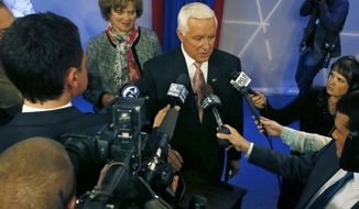 Republican Governor Tom Corbett, center, stands with his wife Susan, as he answers questions after a debate with Democratic party candidate for governor of Pennsylvania, Tom Wolf at the WTAE-TV studio in Wilkinsburg, Pa. on Wednesday, Oct. 8, 2014. (AP Photo/Keith Srakocic)