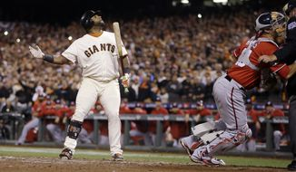 San Francisco Giants Pablo Sandoval watches after a pitch went wild as he signals to Joe Panik on third to come in to score in the seventh inning against the Washington Nationals during Game 4 of baseball's NL Division Series in San Francisco, Tuesday, Oct. 7, 2014. (AP Photo/Ben Margot)