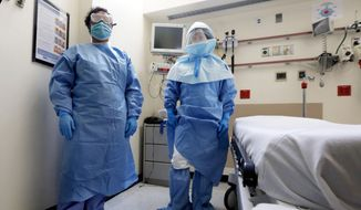 Bellevue Hospital nurse Belkys Fortune, left, and Teressa Celia, Associate Director of Infection Prevention and Control, pose in protective suits in an isolation room, in the Emergency Room of the hospital, during a demonstration of procedures for possible Ebola patients, Wednesday, Oct. 8, 2014. The U.S. government plans to begin taking the temperatures of travelers from West Africa arriving at five U.S. airports, including the New York area's JFK International and Newark Liberty International, as part of a stepped-up response to the Ebola epidemic. (AP Photo/Richard Drew)