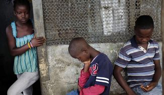 In this photo taken Sunday, Sept. 28, 2014, Promise Cooper, 16, Emmanuel Junior Cooper, 11, and Benson Cooper, 15, sit at their St. Paul Bridge home in Monrovia, Liberia. The Cooper children are now orphans, having lost their mother Princess in July, and their father Emmanuel in August. Their 5-month-old baby brother Success also succumbed to the virus in August. Ruth, their 13-year-old sister is being hospitalized with Ebola. The three never fell sick to the deadly disease. (AP Photo/Jerome Delay)