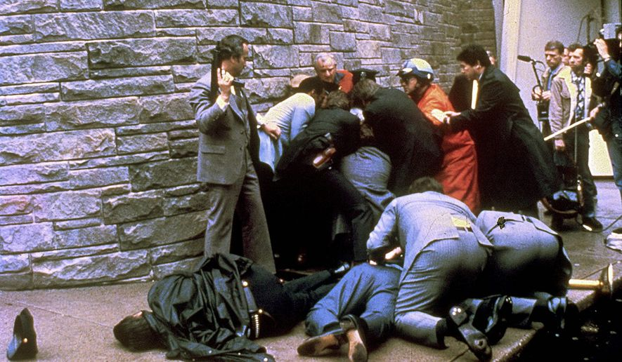 Secret Service agents restrain John W. Hinkley Jr. in the aftermath of his shooting President Reagan outside the Washington Hilton. (Associated Press)