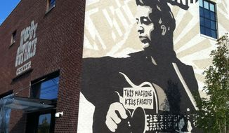 This Sept. 26, 2014 photo shows the Woody Guthrie Center in Tulsa, Oklahoma's Brady Arts District. Guthrie was an Oklahoma native and the center honors his life and legacy. You'll have to pay to visit the museum but the evocative mural outside lends a distinctive feel to the neighborhood. The Brady Arts District has a trendy, hipster vibe and is dotted with art and music venues, along with cafes and bars. (AP Photo/Beth J. Harpaz)