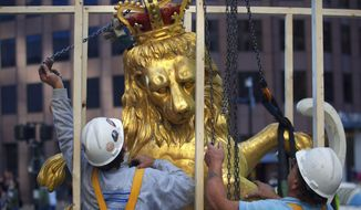 In this Sept. 14, 2014, file photo, a lion statue is removed from atop the Old State House on Washington Street in Boston. The Bostonian Society on Thursday Oct. 9, 2014, hopes to delicately remove a time capsule that has been sealed inside the lion's head since 1901. (AP Photo/The Boston Globe, Dina Rudick) ** FILE **