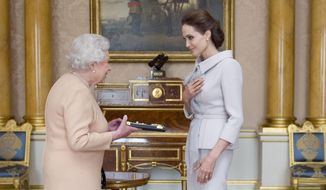 U.S. actress Angelina Jolie, right, is presented with the Insignia of an Honorary Dame Grand Cross of the Most Distinguished Order of St. Michael and St. George by Britain's Queen Elizabeth II at Buckingham Palace, London, Friday, Oct. 10, 2014. Jolie received an honorary damehood (DCMG) for services to U.K. foreign policy and the campaign to end war zone sexual violence. (AP Photo/Anthony Devlin, pool)