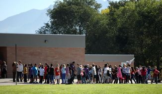 FILE - In this Sept. 11, 2014 file photo, students line up to go back inside after recess at Westbrook Elementary School in Taylorsville, Utah. A Utah schoolteacher who was injured by fragments from a bullet and a porcelain toilet when her gun accidentally went off in a faculty bathroom has been charged with a misdemeanor and resigned. Online court records show 39-year-old Michelle Montgomery was charged this month with discharge of a firearm in a prohibited area within city limits. An arraignment is scheduled for Nov. 5.(AP Photo/The Deseret News, Kristin Murphy, File)  SALT LAKE TRIBUNE OUT;  MAGS OUT