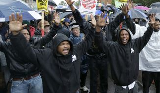 """Protesters chant, """"Hands Up, Don't Shoot"""" as they march in the streets of Clayton, Mo. on Friday, Oct. 10, 2014 near the St. Louis County Courthouse during a protest against the Aug. 9, 2014 police shooting of unarmed black 18-year-old Michael Brown in Ferguson, Mo. Protesters want prosecutors to file criminal charges against the white police officer who fatally shot Brown. (AP Photo/Charles Rex Arbogast)"""