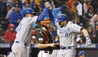 Kansas City Royals' Mike Moustakas (8) celibates with Salvador Perez after Moustakas hits a two-run home run during the 10th inning of Game 1 of the American League baseball championship series against the Baltimore Orioles Saturday, Oct. 11, 2014, in Baltimore. (AP Photo/Alex Brandon)