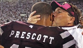 Mississippi State coach Dan Mullen kisses quarterback Dak Prescott after No. 3 Mississippi State defeated No. 2 Auburn 38-23 in an NCAA college football game in Starkville, Miss., Saturday, Oct. 11, 2014. (AP Photo/Jim Lytle)