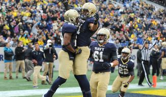 Navy's Geoffrey Whiteside, left, celebrates his 4-yard touchdown run with Brendan Dudeck during the first quarter of an NCAA college football game against VMI Saturday, Oct. 11, 2014, in Annapolis, Md. (AP Photo/Capital Gazette, Paul W. Gillespie)