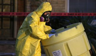 A hazmat worker moves a barrel while finishing up cleaning outside an apartment building of a hospital worker, Sunday, Oct. 12, 2014, in Dallas. The Texas health care worker, who was in full protective gear when they provided hospital care for Ebola patient Thomas Eric Duncan, who later died, has tested positive for the virus and is in stable condition, health officials said Sunday. (AP Photo/LM Otero)