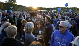 Hundreds of people gather in the setting sun, for an anti-bullying rally unday, Oct. 12, 2014, in Sayreville, N.J.The central New Jersey town thas been rocked by allegations of hazing on its football team that prompted the cancellation of the rest of the season. Organizers say the goal of the event is to promote unity and healing within the community, as well as to show support for the victims of bullying. (AP Photo/Mel Evans)
