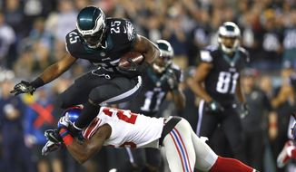 Philadelphia Eagles running back LeSean McCoy (25) is hit by New York Giants strong safety Antrel Rolle (26) during the first half of an NFL football game, Sunday, Oct. 12, 2014, in Philadelphia. (AP Photo/Matt Rourke)