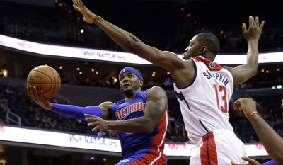 Detroit Pistons forward Josh Smith (6) shoots in front of Washington Wizards center Kevin Seraphin (13), from France, in the first half of a preseason NBA basketball game Sunday, Oct. 12, 2014 in Washington. (AP Photo/Alex Brandon)