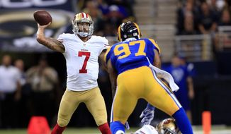 San Francisco 49ers quarterback Colin Kaepernick (7) passes as running back Carlos Hyde blocks St. Louis Rams defensive end Eugene Sims (97) in the second quarter of an NFL football game Monday, Oct. 13, 2014, in St Louis. (AP Photo/Billy Hurst)