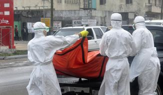 Health workers in protective gear load a body of a person suspected to have died from Ebola on the street of Monrovia, Liberia, Monday, Oct. 13, 2014. (AP Photo/ Abbas Dulleh)